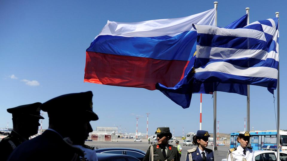 Greek police and army officers stand by Greek, Russian and EU flags as they wait for the arrival of Russian President Vladimir Putin in Athens, Greece airport, May 27, 2016.