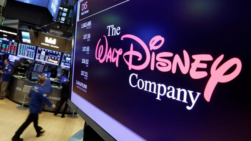 In this August 7, 2017 photo, The Walt Disney Co. logo appears on a screen above the floor of the New York Stock Exchange.