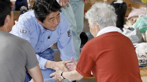 Abe visits flood-hit western Japan as deaths reach 176