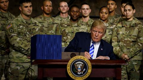 Trump signs defence policy bill with softened China measures
