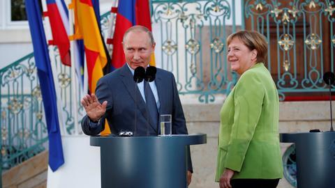 Putin, Merkel tackle tough topics in meeting outside Berlin