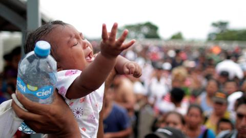 In pictures: Migrant caravan begins to cross into Mexico