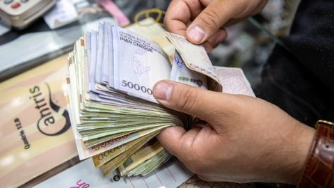 Iran moves to strike four zeroes from its battered currency