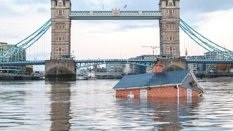 Sinking suburban 'home' drifts down Thames in watery climate protest