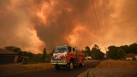 Australian PM defends climate policies as cooler weather helps firefighters