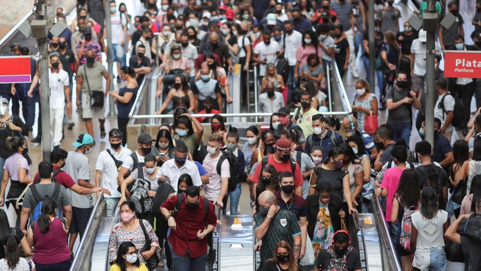 Pessoas usam escadas rolantes depois de descer de um trem na estação Lus em 4 de março de 2021, quando o vírus corona entrou em erupção em São Paulo, Brasil.