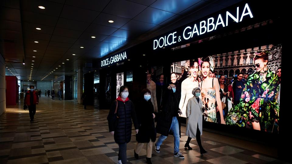 People wearing face masks walk past a Dolce & Gabbana store at a shopping mall in Wuhan, Hubei province on March 30, 2020.