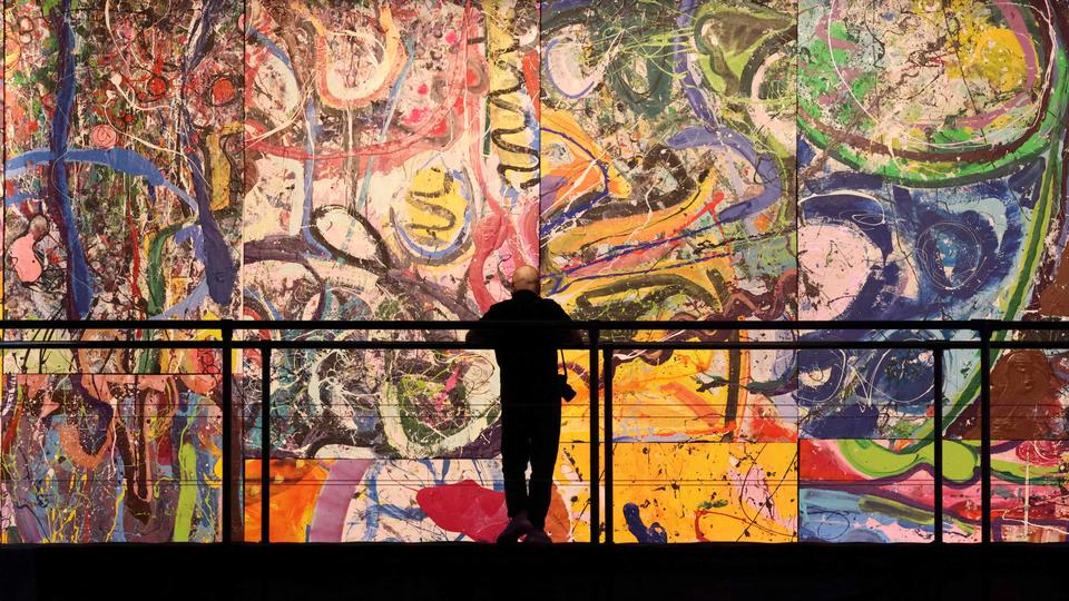 A visitor stares at fragments of Dubai-based British contemporary British artist Sacha Jafri's painting entitled 'The Journey of Humanity', in the Emirati city of Dubai, on February 25, 2021.