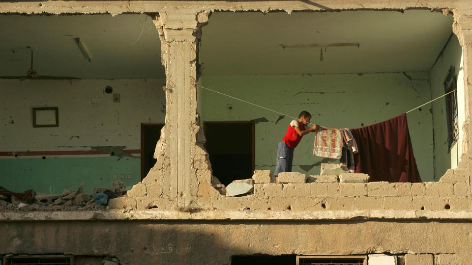 A Palestinian boy hangs laundry inside a damaged house, hit in January 2009 during Israel's military offensive in Gaza, in the Rafah refugee camp, southern Gaza Strip, Thursday, July 2, 2009.