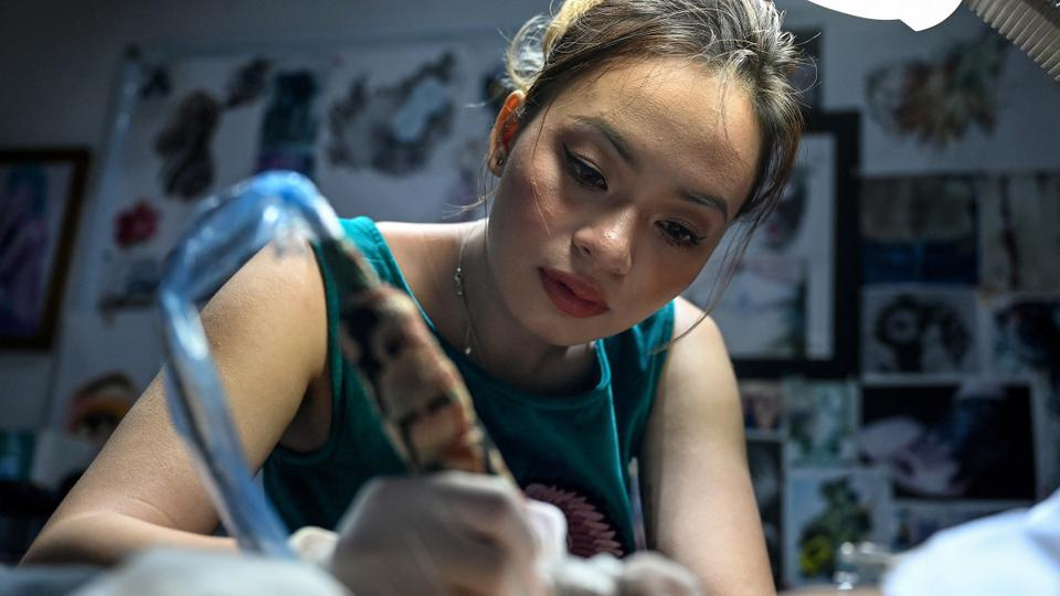 This photograph taken on March 20, 2021, shows tattoo artist Ngoc Like designing a tattoo over a female customer's scar at her studio in Hanoi.