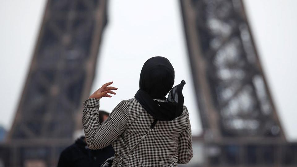 A woman wearing a hijab walks at Trocadero square near the Eiffel Tower in Paris, France, on May 2, 2021.