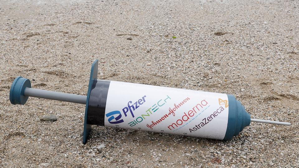 A vaccine prop is seen during a protest by Oxfam activists, on a beach near Falmouth, outside the G7 summit in Cornwall, Great Britain, on 11 June 2021.