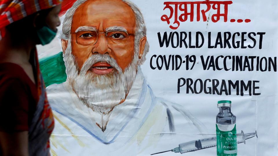 A woman walks past a painting of Indian Prime Minister Narendra Modi a day before the inauguration of the Covid-19 vaccination drive, on a street in Mumbai, India, January 15, 2021.