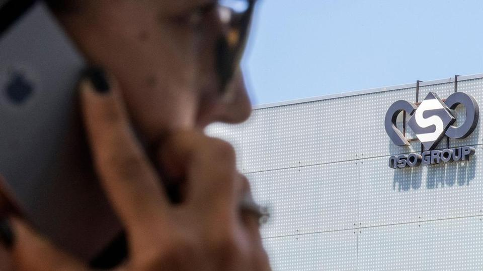 In this file photo taken on August 28, 2016, an Israeli woman uses her iPhone in front of the building housing the Israeli NSO group, in Herzliya, near Tel Aviv.