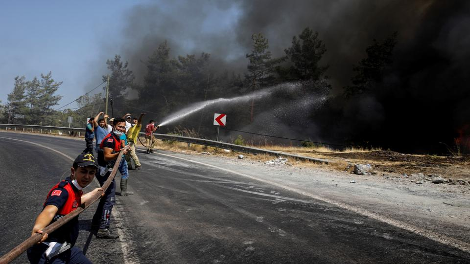 Firefighters and volunteers try to extinguish a wildfire near Marmaris, Turkey