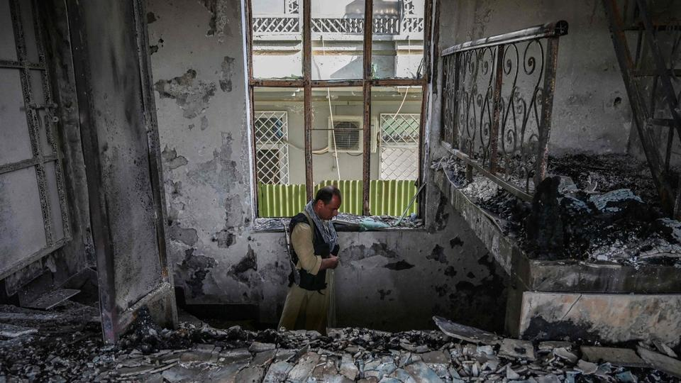 An Afghan security personnel inspects inside a building at the site of a car bomb explosion in Kabul on August 4, 2021.