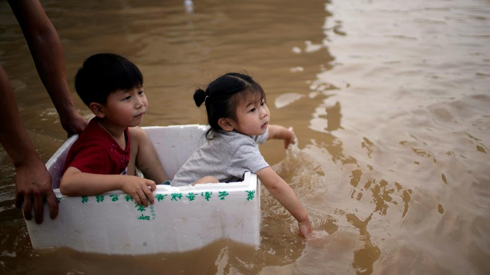 Children sit in a styrofoam container on a flooded road following heavy rainfall in Zhengzhou, Henan province, China July 22, 2021.