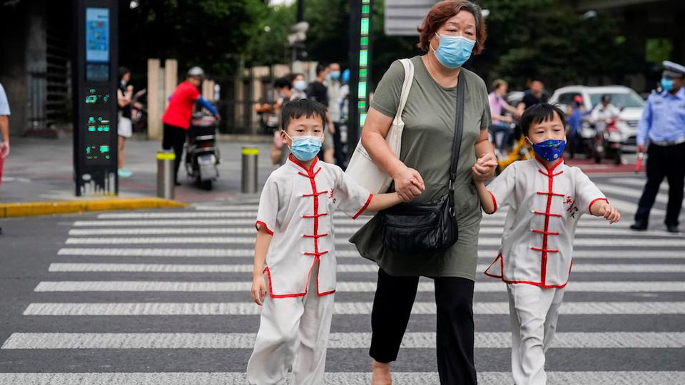 People wearing protective masks walk on a street, following new cases of the coronavirus disease, in Shanghai, China, August 10, 2021.