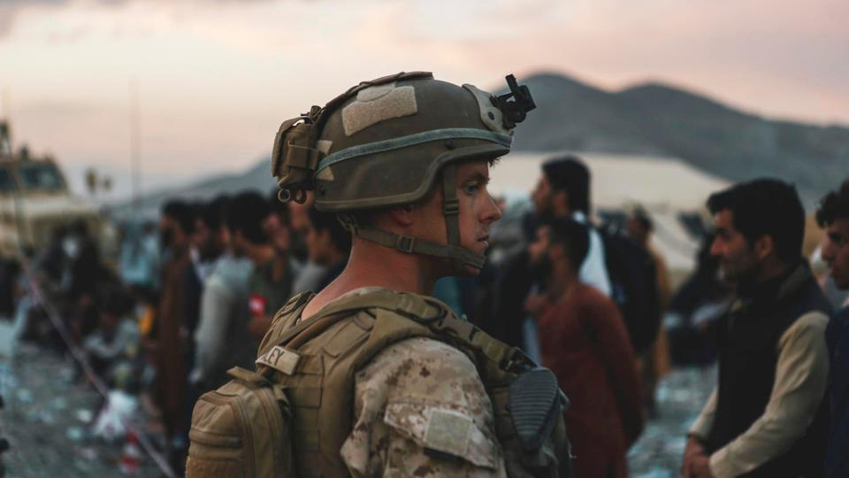 A US Marine assists evacuees during an evacuation at Hamid Karzai International Airport in Kabul, Afghanistan, August 20, 2021.