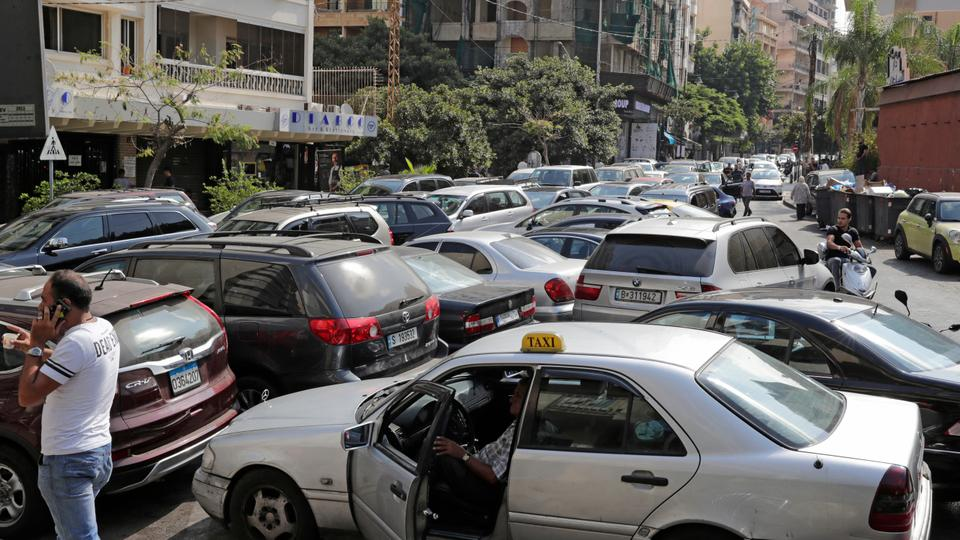 Lebanese wait in a queue outside a closed petrol station in Beirut's Hamra district, August 20, 2021.