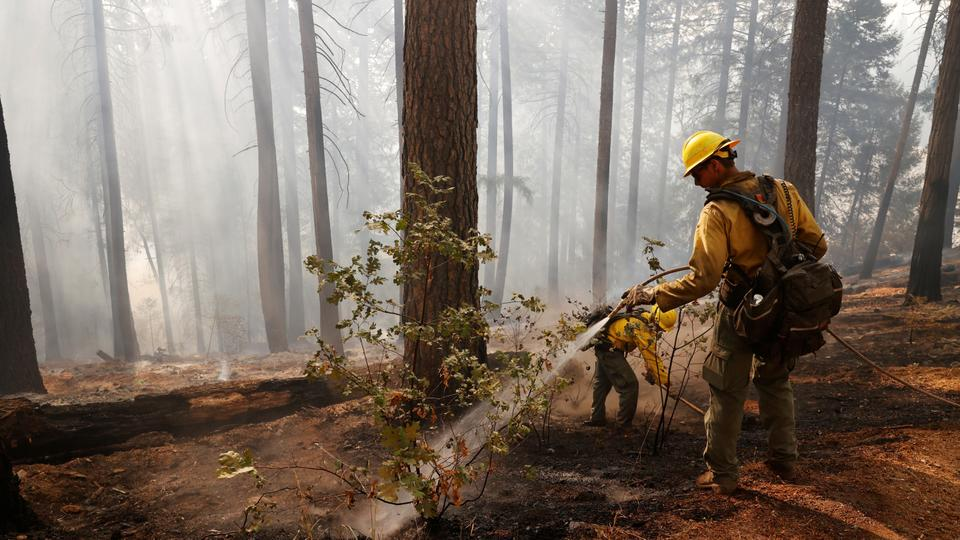 US Fish and Wildlife Service firefighters look for hotspots after a flare-up in Pollock Pines, California, US, August 23, 2021.