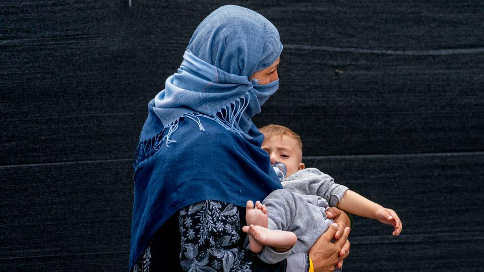 A woman evacuated from Afghanistan steps off a bus with a baby at a processing centre in Chantilly after arriving on a flight at Dulles International Airport, August 23, 2021.