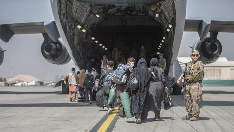 Families begin to board a US Air Force C-17 Globemaster III transport plane during an evacuation at Hamid Karzai International Airport, Afghanistan, August 23, 2021.