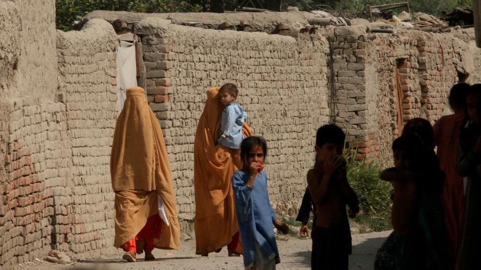 An Afghan refugee women and children walk in an alley at a Khazana refugee camp on the outskirts of Peshawar, Pakistan, June 19, 2021.