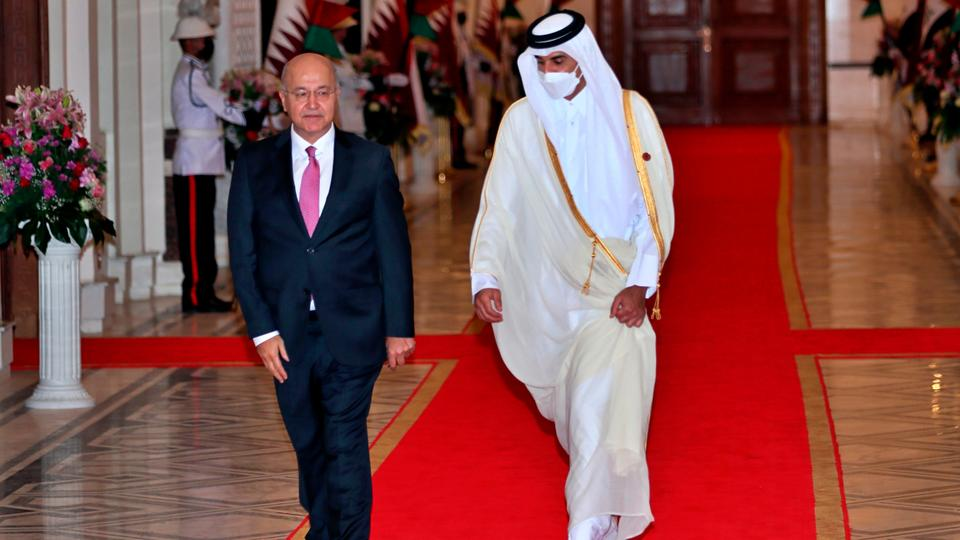 Iraqi President Barham Salih, left, welcomes Qatar's Emir Sheikh Tamim bin Hamad Al Thani in Baghdad's Presidential Palace, August 28, 2021.