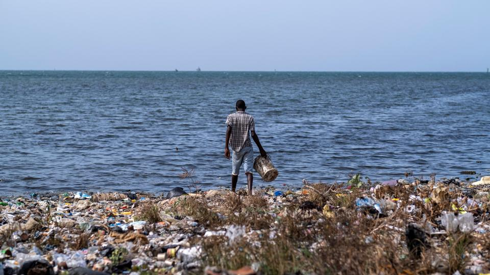 A kid enters a polluted beach to collect with a bucket in Cap-Haitien, Haiti July 21, 2021.