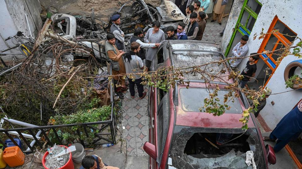 Afghan residents and family members of the victims gather next to a damaged vehicle inside a house, day after a US drone airstrike in Kabul