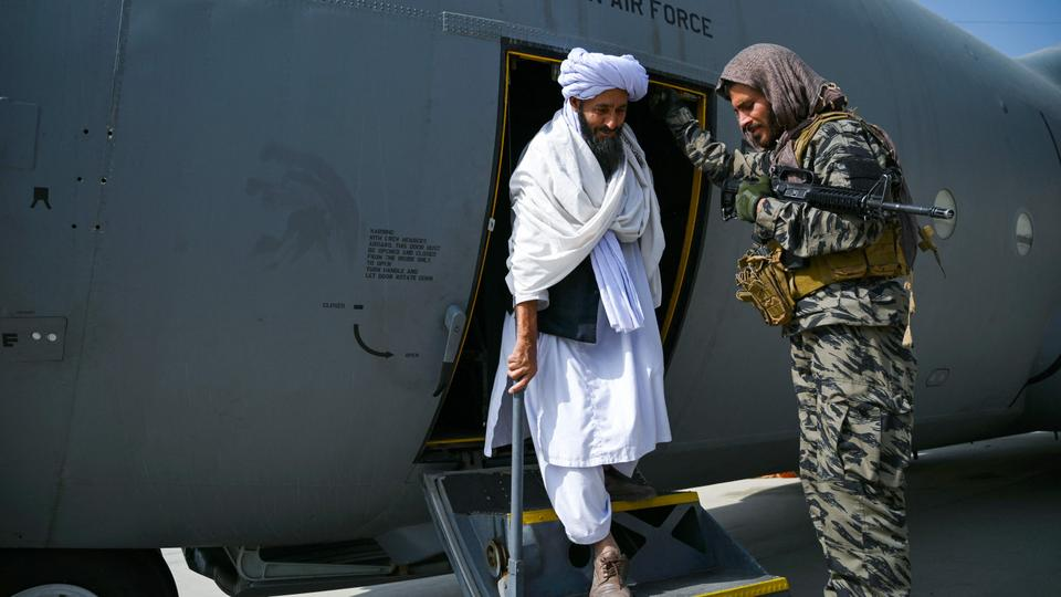 A member of the Taliban (C) walks out of an Afghan Air Force aircraft at the airport in Kabul