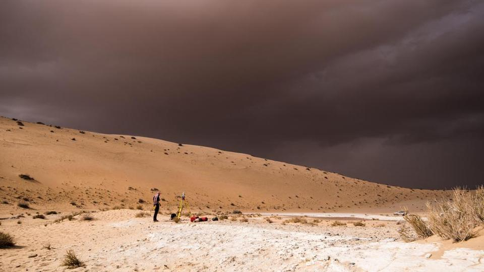 In this undated photo provided by the Palaeodeserts Project in September 2021, a storm arrives during an archaeological excavation of the remains of an ancient lake in northern Saudi Arabia, where ancient humans lived alongside animals such as hippos.