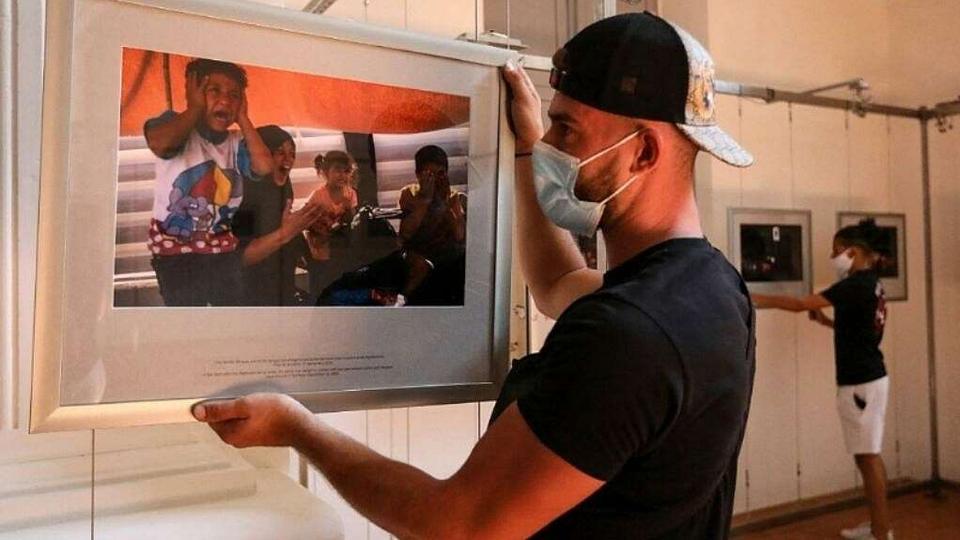 A man hangs photos for exhibition
