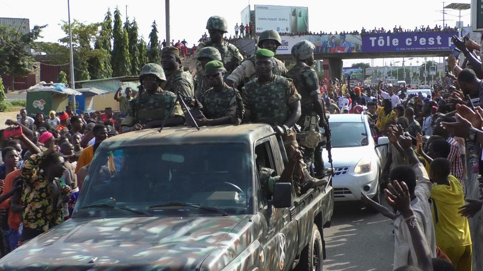 Residents cheer at army soldiers as they celebrate the uprising in Conakry, Guinea on September 5, 2021.