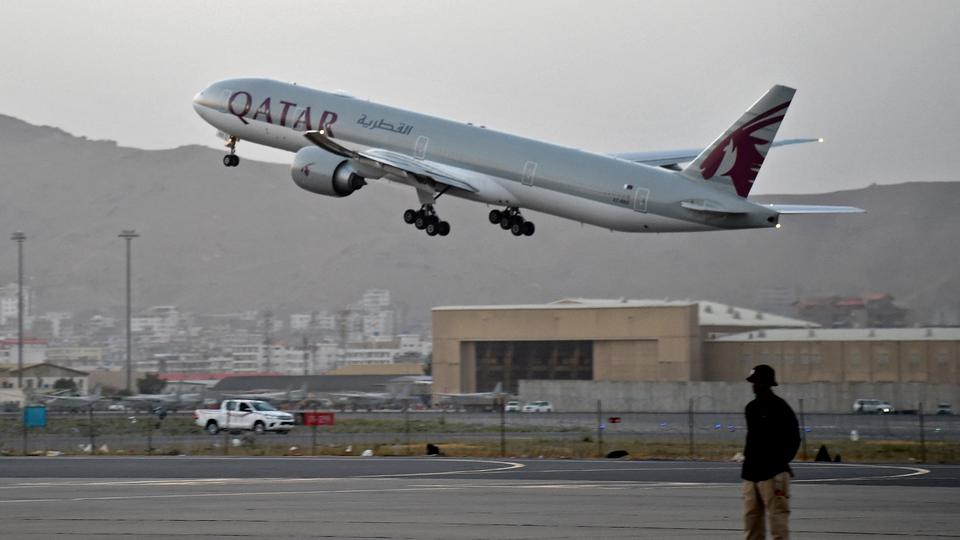 A Qatari security guard  watches as a Qatar Airways aircraft takes off from the airport in Kabul on September 9, 2021.