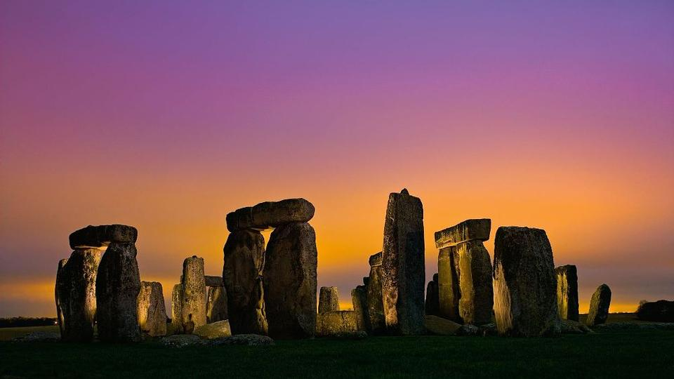 Lights in nearby Amesbury set low-hanging clouds aglow over Stonehenge.