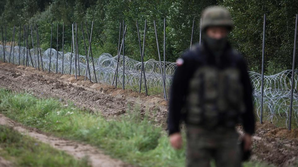 A Polish soldier walks past a barbed wire fence under construction on the border with Belarus in Zubrzyca Wielka near Bialystok, eastern Poland in August 2021.