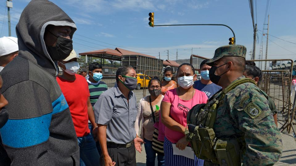 Relatives of inmates speak with a soldier as they wait for information outside a prison in Guayaquil, Ecuador, on September 29, 2021, after a riot occurred.
