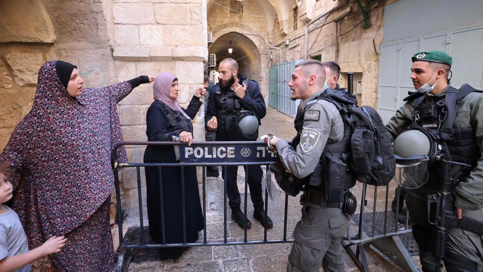 Two women gestures as Israeli police stand guard outside the Al-Aqsa mosque after a woman, who tried to stab officers, was fatally shot in Jerusalem's Old City on September 30, 2021.