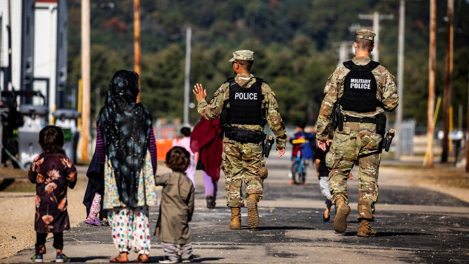 US Military Police walk past Afghan refugees at the Village at Fort McCoy US Army base, in Wisconsin, US on September 30, 2021