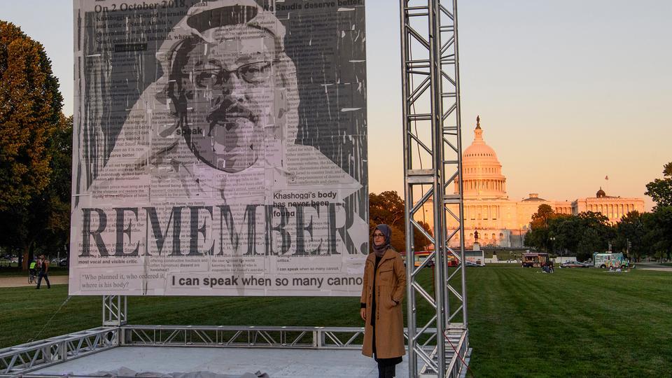 Turkish writer Hatice Cengiz (R), fiancee of Jamal Khashoggi, poses next to a portrait of Khashoggi in Washington, DC, on October 1, 2021.
