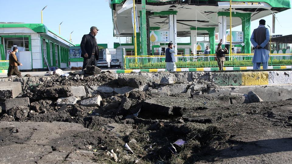 Afghan men walk past from the site of a suicide bomb attack in Kabul, Afghanistan April 21, 2021.