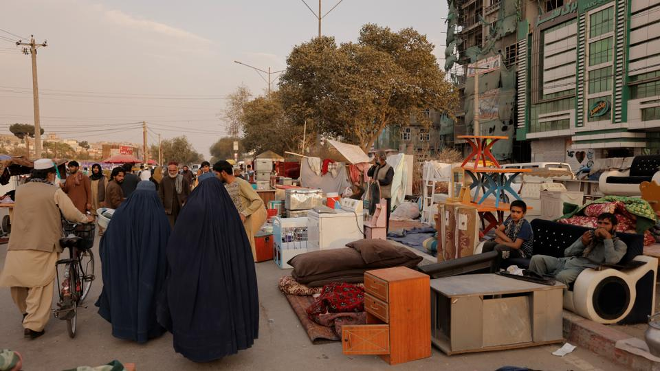 People walk through a second hand market where people leaving the country sell their home appliances and other belongings, in Kabul, Afghanistan October 2, 2021.