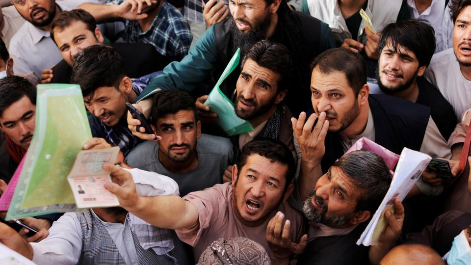 Afghans gather outside the passport office after Taliban officials announced they will start issuing passports to its citizens again, following months of delays that hampered attempts by those trying to flee the country after the Taliban seized control, in Kabul, Afghanistan on October 6, 2021.