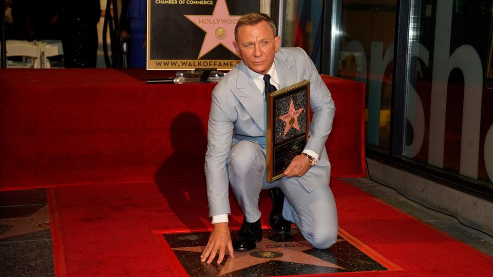 Daniel Craig poses atop his new star on the Hollywood Walk of Fame while holding a replica of the star during a ceremony in his honour on October 6, 2021, in Los Angeles.