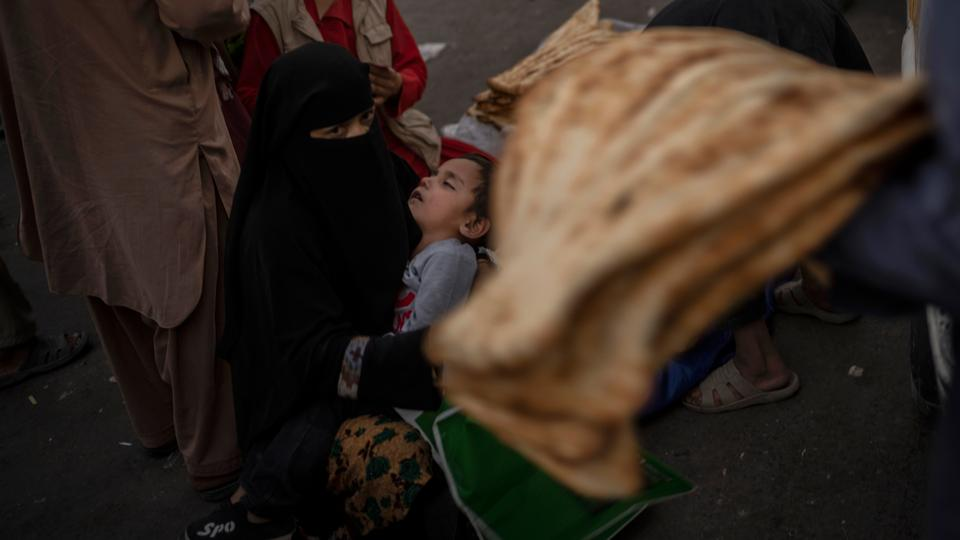 An Afghan woman begs at a market in Kabul's Old City, Afghanistan, on September 14, 2021.