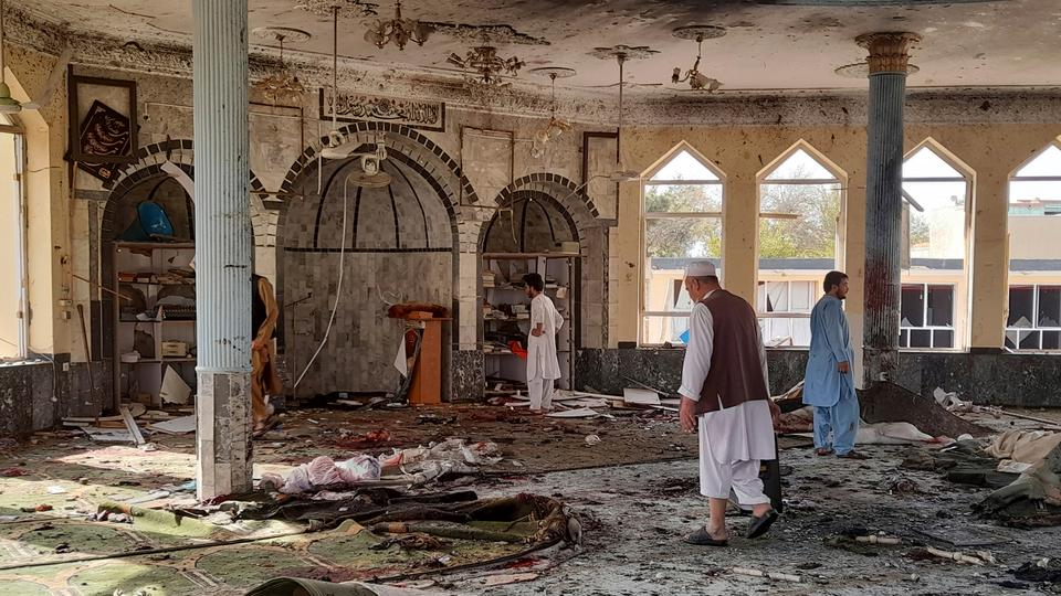 People inspect the inside of a mosque following a bombing in Kunduz province northern Afghanistan on October 8, 2021.