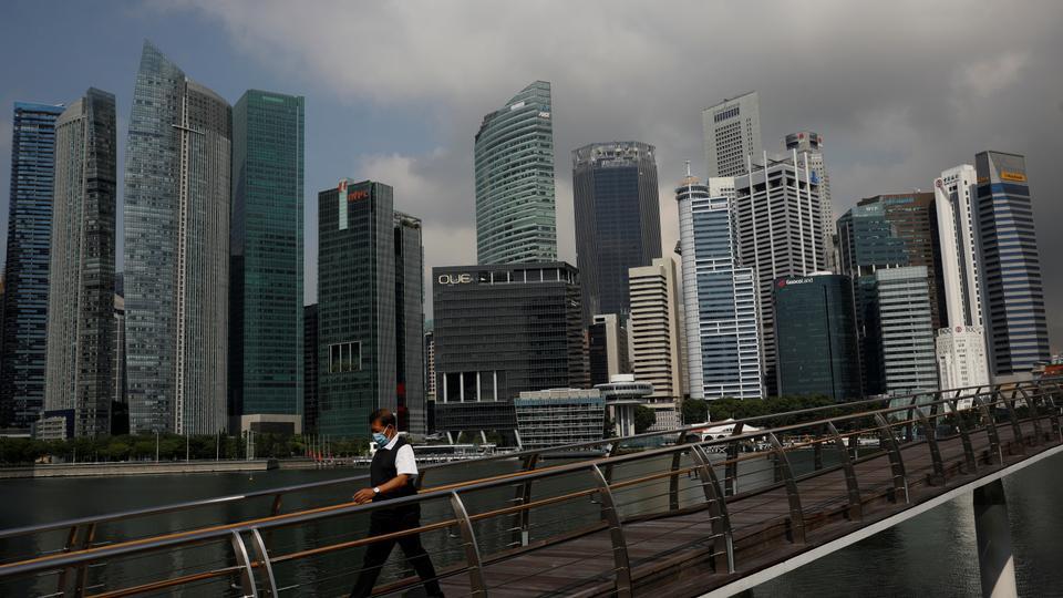 A man passes the city skyline during the coronavirus disease, in Singapore, September 29, 2021.