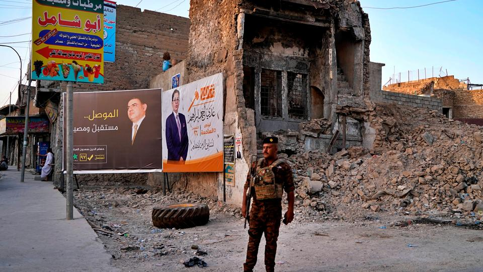 An Iraqi federal policeman stands guard near campaign posters for parliamentary elections in Mosul, Iraq, October 3, 2021.